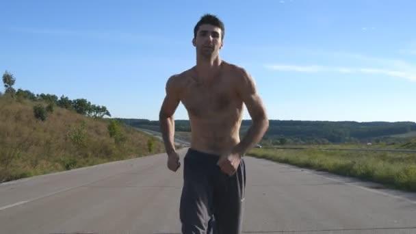 Uomo del corridore sprint jogging in autostrada. Atleta di sport uomo allenamento allaperto in estate. Giovane ragazzo muscolare forte che si esercita sulla strada rurale durante lallenamento. Attivo stile di vita sano allesterno. Chiuda in su