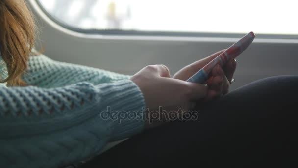 Fiatal lány utazik a vonaton, és a mobiltelefon használata. Gyönyörű nő küld egy üzenetet a smartphone. Beszélgetni a barátokkal, a vonzó lány