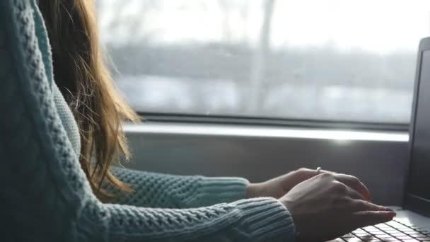 Psaní na klávesnici notebooku ve vlaku ženské ruce. Žena, chatování s přáteli během cestování na železnici. Mladá dívka pomocí poznámkového bloku. ARM vytisknout zprávu. Detailní záběr