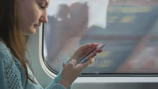 Mladá dívka na cestách ve vlaku a pomocí mobilního telefonu. Krásná žena pošle zprávu od smartphone. Atraktivní dívka, chatování s přáteli. Míjení vlaku na okna. Detailní záběr