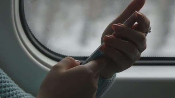 Fiatal nő utazik a vonaton, és a mobiltelefon használata. Női kéz küld egy üzenetet a smartphone. Kar, lány, csevegni a barátaival. Közelről