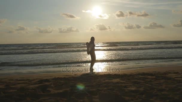 Fiatal, boldog asszony sállal, spinning, és fordult, kerek az óceán tengerparton naplementekor. Lány élvezi nyári. Női sziluett bikini repülő sál, kezében séta a tenger partján. Lassú mozgás