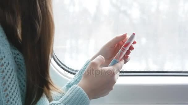 Fiatal lány utazik a vonaton, és a mobiltelefon használata. Gyönyörű nő küld egy üzenetet a smartphone. Női kezek és beszélgetni a barátokkal. Lassú mozgás közelről