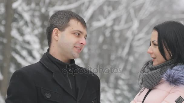 Mladá hezká brunetka a její přítel chatování v parku. Milovníky stojí v parku a hovor, smích, polibek