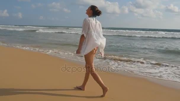 Krásná žena v plavkách a tričko walking na moře pláž naboso a zvedl ruce. Mladá dívka jde na břehu oceánu a užívat si léta. Mořské vlny na pozadí. Koncept dovolenou