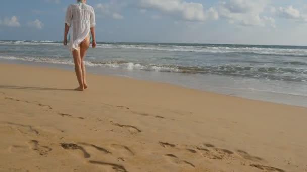 Szép nő, fürdőruha és ing séta a tengerparttól mezítláb. Fiatal lány megy az óceán partján. Női lábra rálép a homok, a tenger hullámai háttér. Nyári vakáció koncepció hátulnézet
