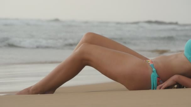 Beautiful young sexy woman lying on golden sand on sea beach and relaxing during summer vacation travel. Close up