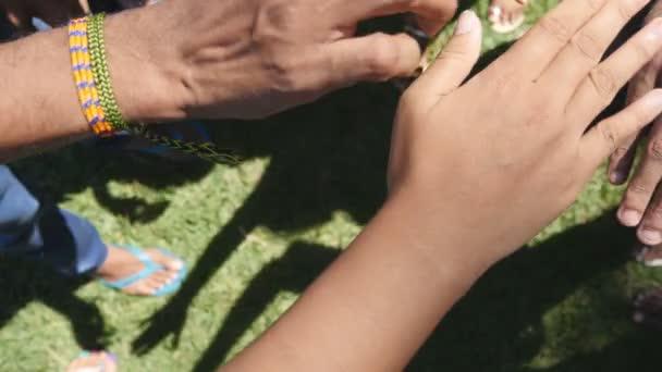 Arm aller Rassen und Farben nach und nach in Einheit und Teamarbeit zusammengestapelt und dann angehoben. viele multirassische Hände, die sich im Zentrum eines Kreises versammeln und dann jubeln. Nahaufnahme im Freien