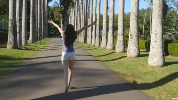 Young beautiful woman jogging and spinning along exotic parkland and having fun. Happy girl is running in tropical park. Freedom travel concept. Summer vacation trip Rear back view