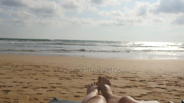 Ženské nohy proti moři. Cestování nohy krásné mladé ženy relaxační na břehu moře během letních prázdnin. Hlediska sexy dívka ležící a opalování na pláži. Detailní záběr