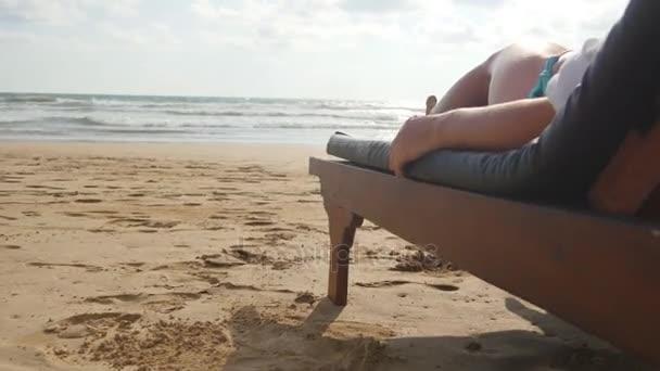 Női test, a kellemes és pihentető nyaralás során a üres homokos ocean beach kanapé longue. Fiatal nő, fekvő szolárium, a tengeri és a szolárium. A lány a bikini üdülőhely. Közelről