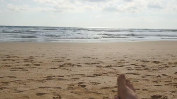 Giovane donna sdraiata sul lettino da mare e abbronzatura. Corpo femminile su chaise-longue relax e godersi durante le vacanze estive sulla spiaggia delloceano di sabbia vuota. Ragazza in bikini su un resort. Chiuda in su