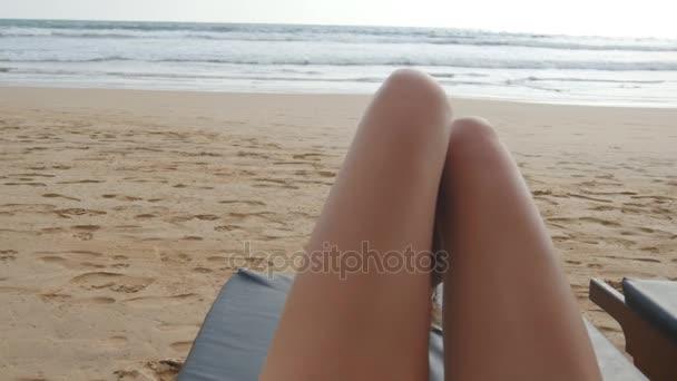 Punto di vista di giovane donna sdraiata sul lettino da mare e abbronzatura. Piedini femminili sulla chaise-longue relax e godersi durante le vacanze estive sulla spiaggia delloceano. Piedi della ragazza su un resort. Chiuda in su Pov