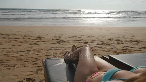 Ženské tělo na lehátko relaxační a těší během letních prázdnin na prázdné písčité mořské pláži. Mladá žena ležící na lehátko, moře a opalování. Dívka v bikinách na resort. Detailní záběr