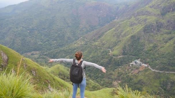 Fiatal női túrázó a hátizsák elérte a felső-hegy és emelt kezek. Nő turisztikai gyönyörű canyon szélén álló, győzedelmesen outstretching arms fel. Lassú mozgás hátsó vissza Nézd
