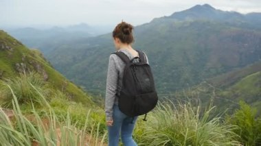 Young woman tourist with backpack walking at trail in mountains with beautiful nature landscape at background. Female hiker going along narrow summit ridge crest. Healthy active lifestyle. Slow motion