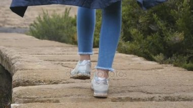 Young female tourist with backpack walking on stone trail outdoor. Legs of woman going on rocky ground at beautiful nature. Girl stepping at mountains during travel. Healthy lifestyle. Slow motion