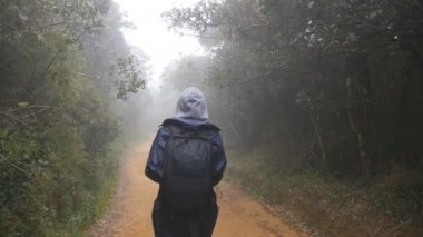 Hiking woman with backpack walking in tropical wet forest. Young girl in raincoat going on wood trail during travel. Follow to female tourist stepping on the jungle path. Slow motion Rear back view