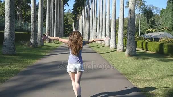 Mladá krásná žena, jogging a otáčí podél exotickým parkem a baví. Šťastná dívka je spuštěn v tropickém parku. Svoboda cestování koncept. Letní prázdninový výlet zadní pohled zezadu. Zpomalený pohyb