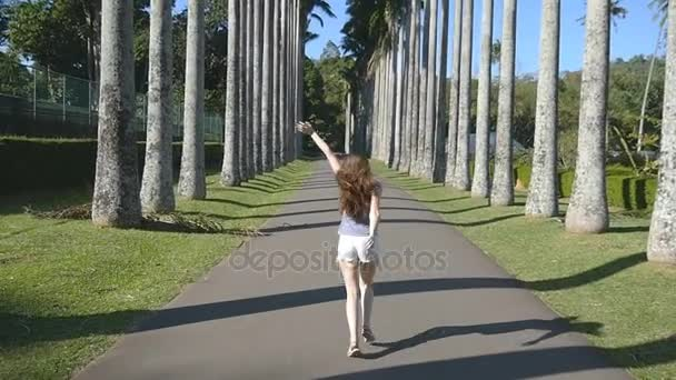 Young beautiful woman jogging and spinning along exotic parkland and having fun. Happy girl is running in tropical park. Freedom travel concept. Summer vacation trip Rear back view. Slow motion