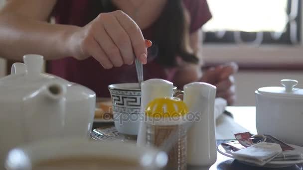 Ženská ruka míchání cukru nebo mléka v šálku horké kávy nebo čaje. Detailní záběr