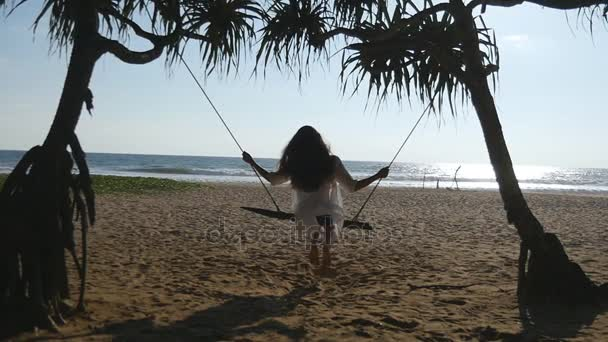 Young happy woman relaxing at swing at tropical ocean beach. Beautiful girl sitting on swing and enjoying summer vacation or holiday. Female having fun at sea shore. Slow motion Rear back view