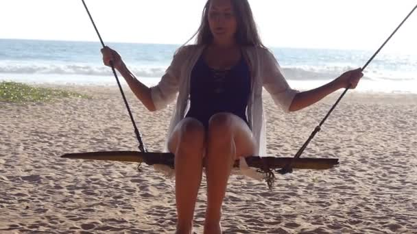 Close up of young happy woman in swimsuit and shirt relaxing at swing at tropical ocean beach. Beautiful girl sitting on swing and enjoying summer vacation. Female having fun at sea shore. Slow motion
