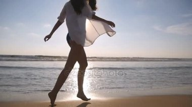 Happy woman walking and playing on the beach near the ocean. Young beautiful girl enjoying life and having fun at sea shore. Summer vacation or holiday. Nature landscape at background. Slow motion