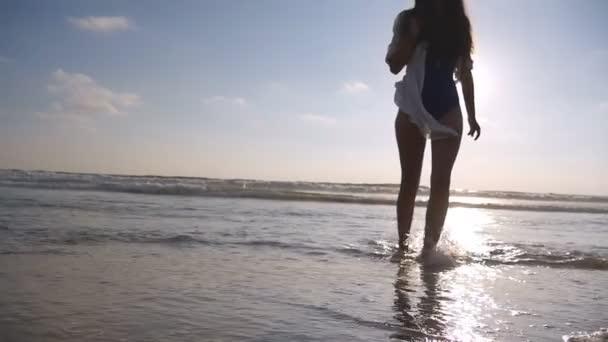Mladá žena v plavkách a košili jít podél oceánu pláži při západu slunce. Dívka si léto. Žena chůze po vodě na břehu moře. Zpomalené Detailní záběr