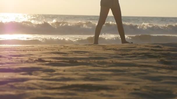 Egy fiatal nő lábai, amint a homokba lép. Közelkép női lábak séta arany homok a strandon, óceán hullámok a háttérben. Mezítlábas lány a tengerparton. Nyári vakáció. Lassú mozgás.