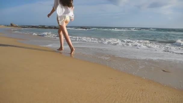 Šťastná žena v bikinách a košili v ocean beach. Krásná mladá dívka, užívat si života a baví u mořského pobřeží. Letní prázdniny nebo dovolenou. Tropická krajina na pozadí. Zpomalený pohyb