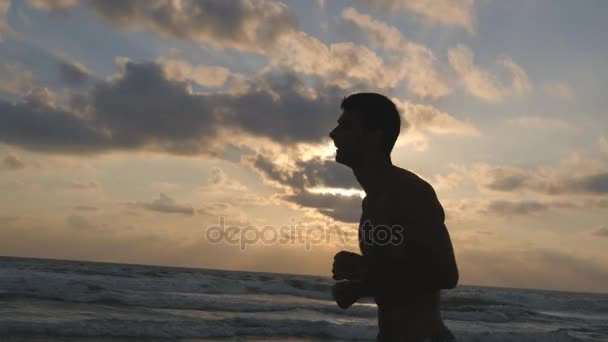 Young sporty man running on the sea beach at sunset. Athletic guy jogging along ocean shore during sunrise. Male sportsman exercising outdoor. Healthy active lifestyle. Workout at nature. Close up