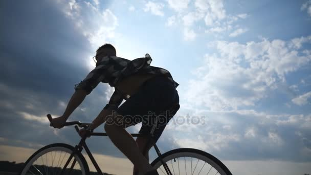 Silueta mladík na koni na vintage kolo s krásného západu slunce na obloze v pozadí. Sportovní chlap na kole v zemi silnici. Muž cyklista jízdní kolo. Zdravý aktivní životní styl zpomalené