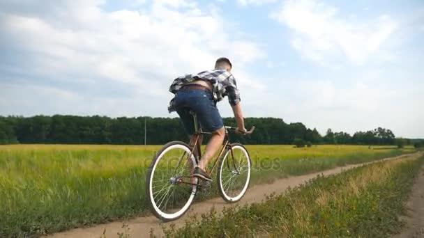 Mladý muž jedoucí na kole vinobraní na venkovské silnici, přes pole. Na kole podél venkovská stezka venkovní sportovní chlap. Muž cyklista jízdní kolo na venkově. Zdravý aktivní životní styl zpomalené