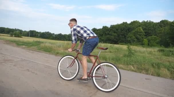 Mladý pohledný muž na koni na Retro kolo v zemi silnici. Sportovní chlap, Cyklistika na venkově stezka. Mužské cyklistu jedoucího pevné ozubené kolo na silnice. Zdravý aktivní životní styl zpomalené