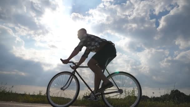Mladý pohledný muž na koni na Retro kolo v zemi silnici. Sportovní chlap, jízda na kole na trati. Mužské cyklistu jedoucího pevné ozubené kolo na silnice. Zdravý aktivní životní styl zpomalené