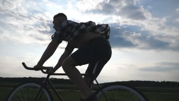 Silueta mladík na koni na vintage kolo s krásného západu slunce na obloze v pozadí. Sportovní chlap na kole v zemi silnici. Mužské cyklistu jedoucího pevné ozubené kolo. Zdravý aktivní životní styl Slowmo