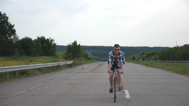 Mladý pohledný muž na koni na Retro kolo v zemi silnici. Sportovní chlap, jízda na kole na trati. Mužské cyklistu jedoucího pevné ozubené kolo na silnice. Zdravý aktivní životní styl zpomalené přední pohled