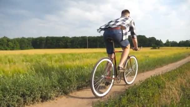 Mladý muž jezdí na veteránském kole na venkovské silnici přes pole. Sportovec, co jezdí na kole po venkovské stezce. Muž cyklista na kole na venkově. Zdravý aktivní životní styl Zpomalený pohyb