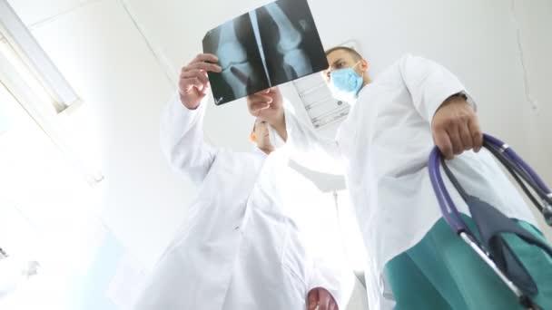 Dva běloši lékaři zobrazit obrázek mri a diskutovat o něm. Zdravotníci v nemocnici zkoumat rentgenové tisků. Mužské lékaři konzultovat s sebou při pohledu na obraz x ray. Nízký úhel pohledu