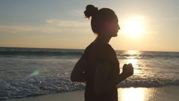 Dívka jogging podél pobřeží oceánu během východu slunce. Silueta mladé ženy běží na pláži moře při západu slunce. Ženské sportovce vykonávající venkovní. Zdravé cvičení aktivní životní styl v přírodě. Zpomalený pohyb