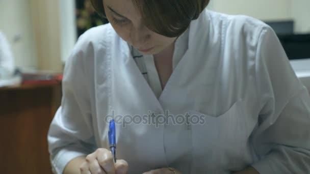 Lékařka, zápisem předpis v nemocnici. Mladá zdravotní sestra pracuje v kanceláři a psaní lékařské záznamy. Pojetí zdravotní péče. Detailní záběr