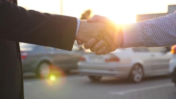 Obchodní handshake venkovní při západu slunce. Dva podnikatelé pozdrav vzájemně parkování. Třesení mužské ruce venku. Kolegové setkat a potřást rukou v městské pozadí. Detailní záběr Zpomalený pohyb