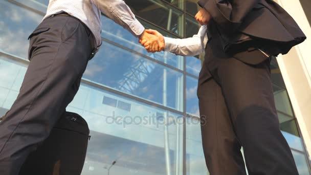 Obchodní handshake venkovní poblíž kancelářská budova. Dva podnikatelé navzájem pozdrav v městském prostředí. Třesení mužské ruce venku. Kolegové setkat a potřást rukou. Detailní záběr Zpomalený pohyb