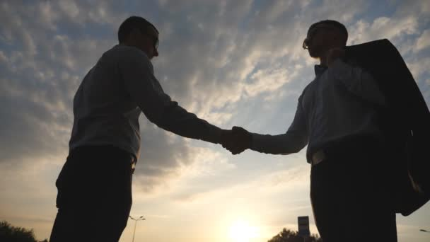 Two young businessmen greeting each other with cloudy sky at background. Business handshake outdoor. Shaking of male arms outside. Colleagues meet and shake hands. Close up Slow motion