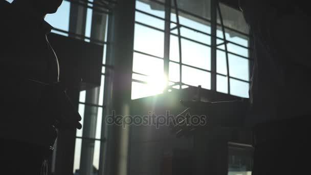 Obchodní handshake krytý v kanceláři s slunce záře na pozadí. Dva podnikatelé pozdrav navzájem. Třesení vnitřní mužské ruce. Kolegové setkat a potřást rukou. Detailní záběr Zpomalený pohyb