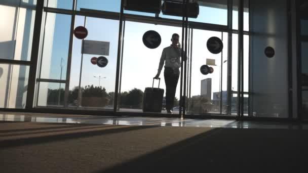 Mladý podnikatel chce letiště s jeho zavazadly a mluví o telefonu. Muž s kufrem. Chlap jde přes skleněné dveře a roll kufr na kolečkách. Výlet nebo cestování koncept. Zpomalený pohyb