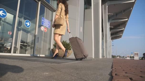 Dívka v podpatcích chodit na letiště a válcování kufr na kolečkách. Obchodní lady zadání jde skleněných dveří se zavazadly. Žena, která nosí oblek případ. Koncept cestování výlet nebo dovolenou. Zpomalený pohyb