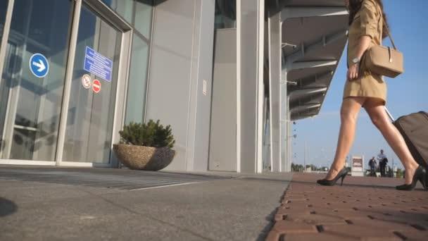 Mladá žena v podpatcích chodit s její kufr na okraji letiště. Obchodní lady letiště se zavazadly. Dívka roll kufr na kolečkách. Koncept cestování výlet nebo dovolenou. Zpomalený pohyb
