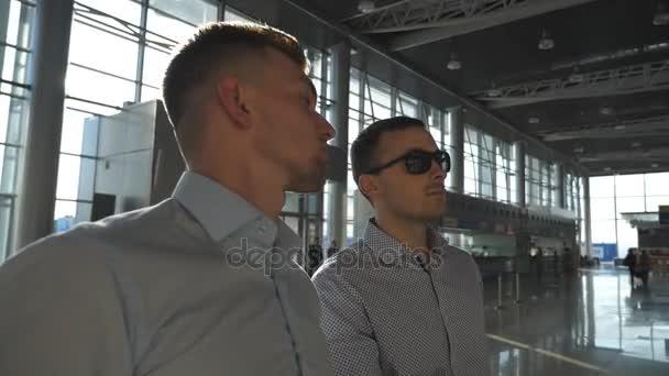 Dva mladí podnikatelé při pohledu na letový řád na letišti. Obchodní muž v sluneční brýle ukazující něco na jeho kolega v harmonogramu Rada obrazovky. Kontroly leteckých společností odchod zpomalené Detailní záběr